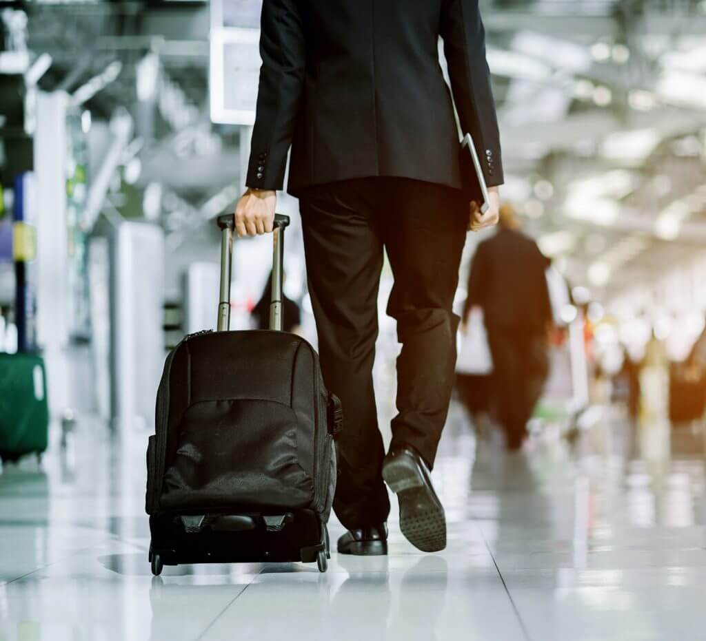 Corporate Traveler Walks through Airport with Luggage