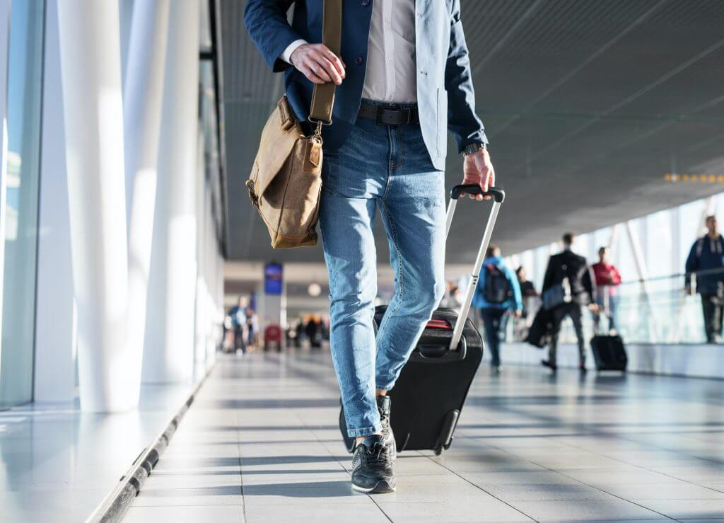 Business Travel Management - Man Walking through Airport With Luggage - Christopherson Business Travel
