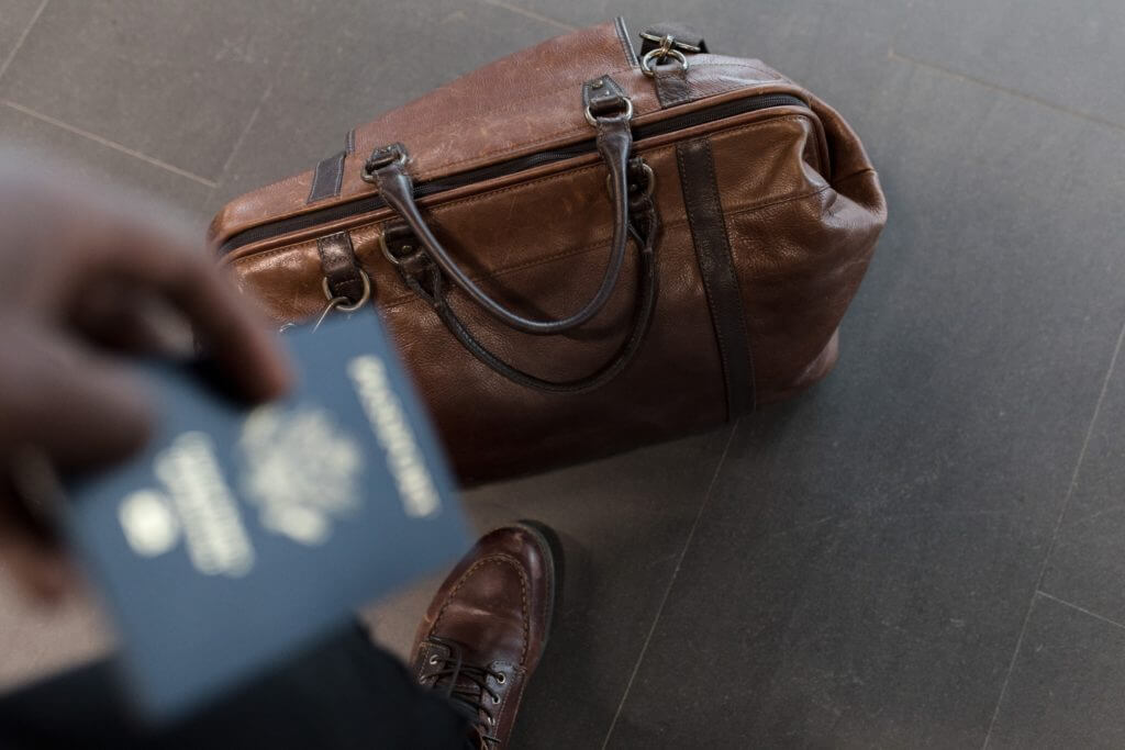 business traveler with a laptop bag and passport using a business travel agency